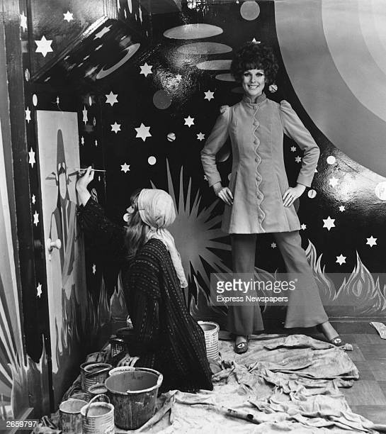 Model Paulene Stone wearing a velvet coat from the Apple boutique standing in front of a night sky backdrop while a set designer paints a figure on...
