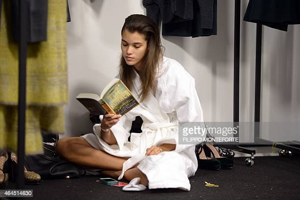 Model Pauline Hoarau reads backstage before the show for Anteprima at the women Fall / Winter 2015/16 Milan's Fashion Week on February 26 2015 AFP...