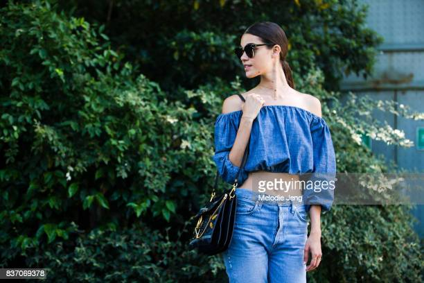 Model Pauline Hoarau wears a blue offshoulder crop top and jeans on July 04 2017 in Paris France