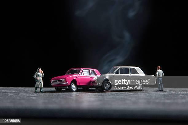 model people standing near toy car crash scene