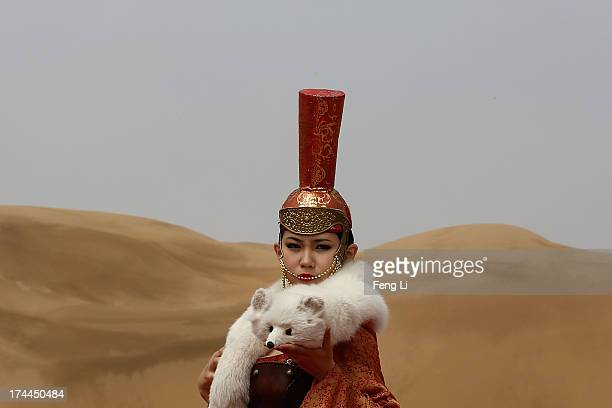 A model performs in Mongolia costumes in Xiangshawan Desert also called Sounding Sand Desert on July 18 2013 in Ordos of Inner Mongolia Autonomous...