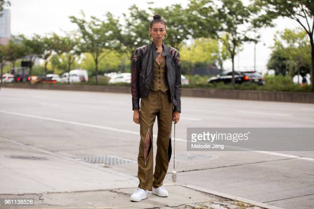 Model Phoenix Anderson wears vintage Alexander McQueen a leather jacket and matching vest top and pants with a zip and white sneakers during New York...