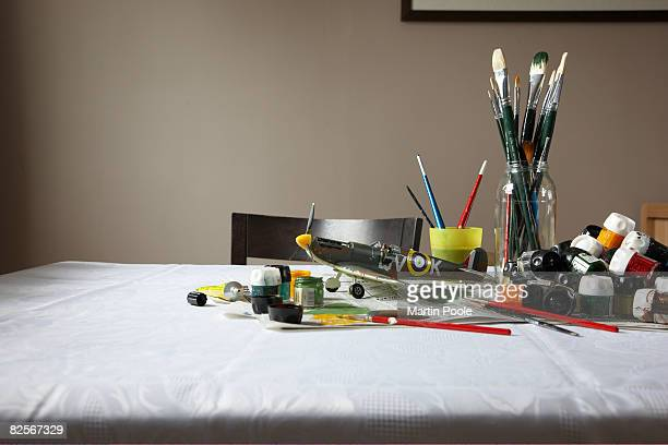 model plane on table with paint and brushes