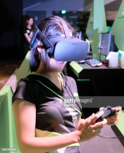 A model plays video games via a visual reality headset during a press conference in Taipei on the eve of the COMPUTEX computer expo in Taipei on May...