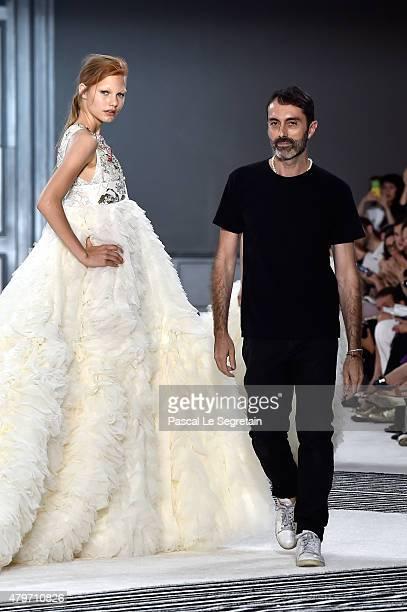 A model pose with designer Giambattista Valli on the runway following the Giambattista Valli show as part of Paris Fashion Week Haute Couture...