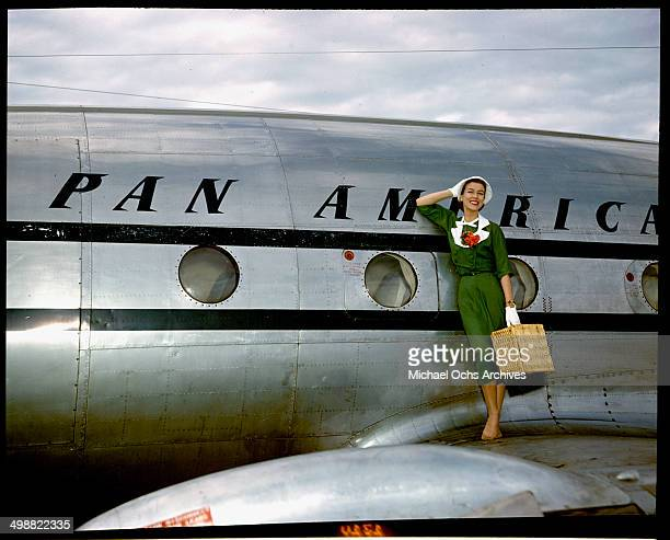 A model poses as a passenger walking off the Pan American Clipper 'Challenge' Lockheed 1049 airliner circa 1947