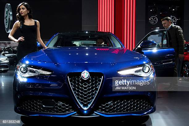 A model poses as men looks at the Alfa Romeo Giulia during the 2017 North American International Auto Show in Detroit Michigan January 9 2017 / AFP /...