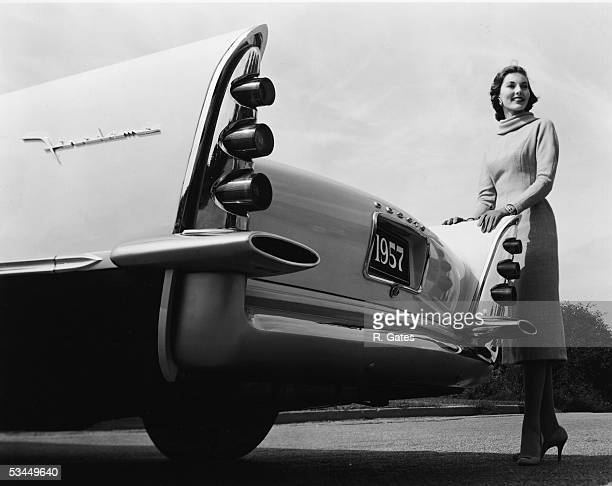 A model poses behind the tailfin of a 1957 DeSoto Firedome S25 sedan 1950s