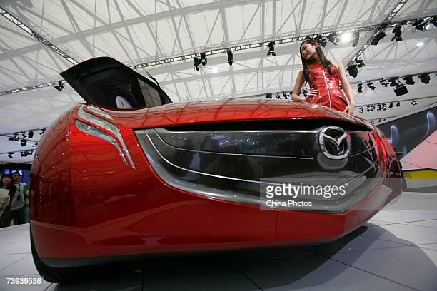 A model poses beside a futuristic looking Mazda concept car during the Auto Shanghai 2007 event on April 20 2007 in Shanghai China More than 1300 car...