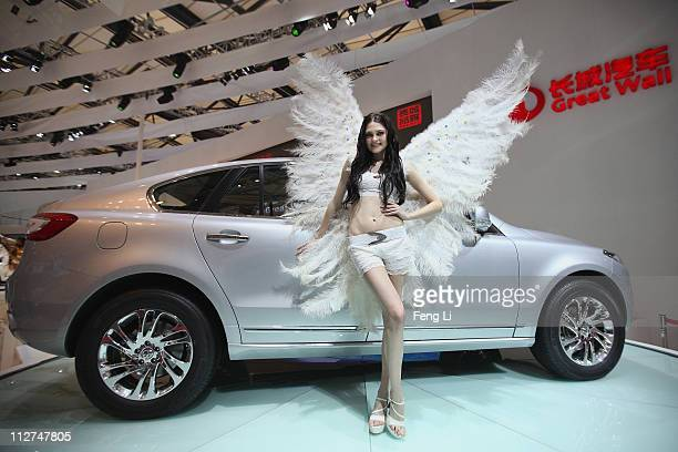 Model poses beside a Great Wall Hover 1F car during the media day of the Shanghai International Automobile Industry Exhibition at Shanghai New...
