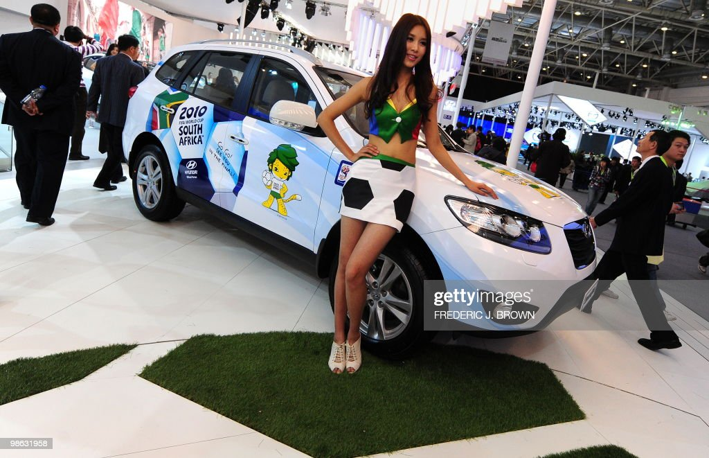 A model poses beside a Hyundai Santa Fe decorated for this summer's football World Cup during a media preview at the Beijng Auto Show on April 23, 2010. Auto sales in booming China hit 13.64 million in 2009, overtaking the United States, as increasingly well-off Chinese consumers continued to snap up cars, helped by government incentives such as lower taxes. AFP PHOTO/Frederic J. BROWN