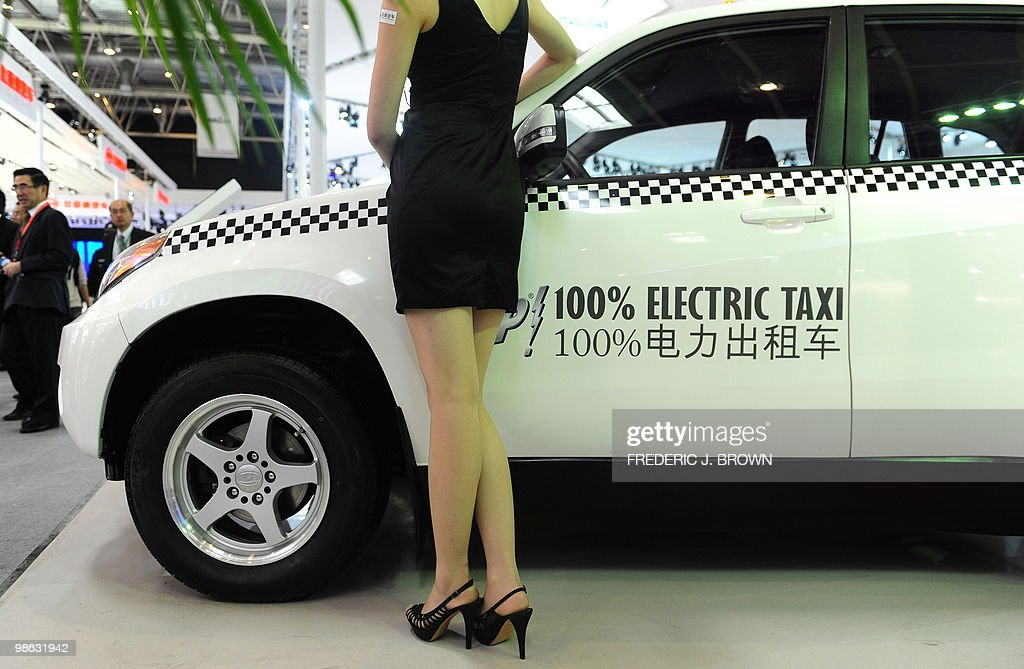 A model poses beside a Jonway Automobile Xixi Sci-Tech Insland Project Electric Taxi during a media preview at the Beijng Auto Show on April 23, 2010. Auto sales in booming China hit 13.64 million in 2009, overtaking the United States, as increasingly well-off Chinese consumers continued to snap up cars, helped by government incentives such as lower taxes. AFP PHOTO/Frederic J. BROWN