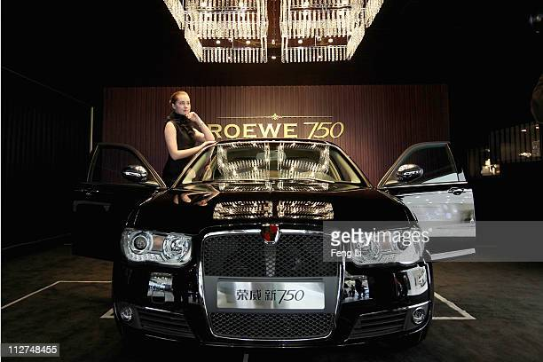 Model poses beside a Roewe 750 car during the media day of the Shanghai International Automobile Industry Exhibition at Shanghai New International...