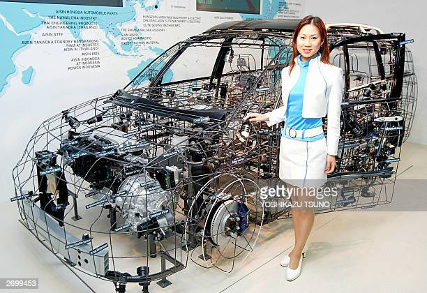 A model poses beside a wire frame vehicle created by Aisin Seiki Toyota Motor group's auto parts maker at the Tokyo Motor Show in Mauhari suburban...