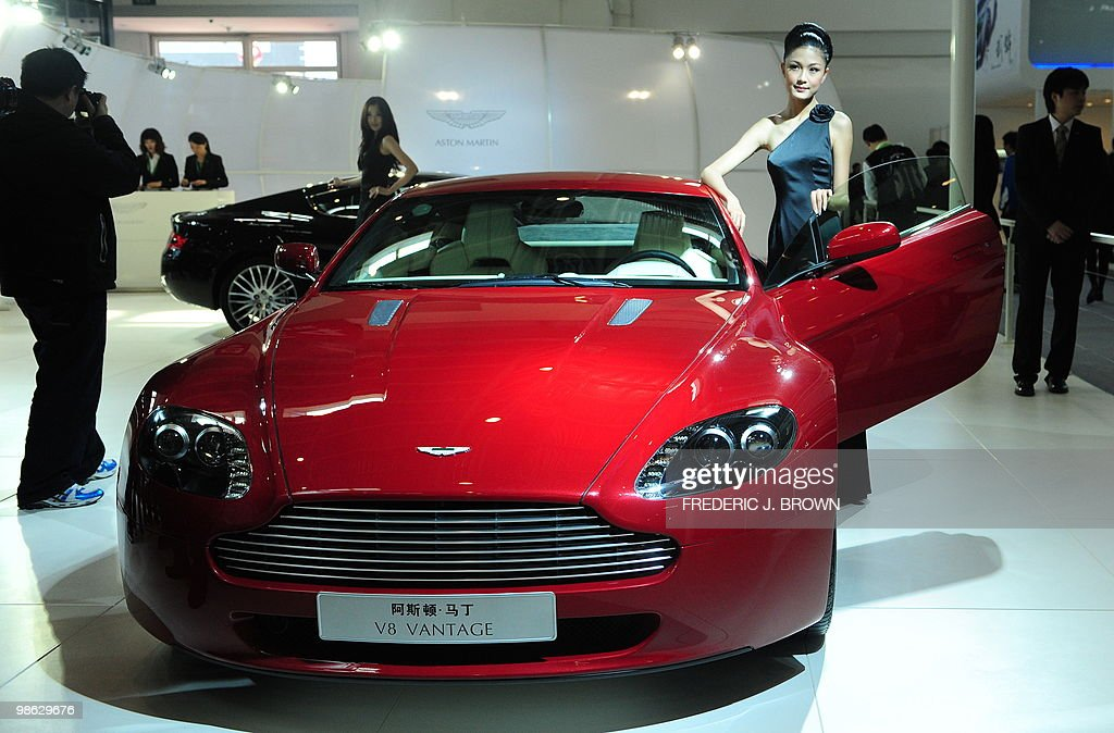 A model poses beside an Aston Martin V8-Vantage during a media preview at the Beiijng Auto Show on April 23, 2010. Auto sales in booming China hit 13.64 million in 2009, overtaking the United States, as increasingly well-off Chinese consumers continued to snap up cars, helped by government incentives such as lower taxes. AFP PHOTO/Frederic J. BROWN