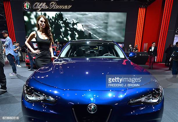A model poses beside the new Alfa Romeo Giulia on display on the first of two press days at the 2016 Los Angeles Autoshow now called Automobility LA...