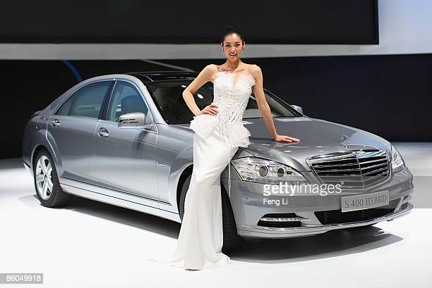 Model poses beside the world premiere display of the Mercedes-Benz S400 Hybrid during a special media opening of the Auto Shanghai 2009 at Shanghai...
