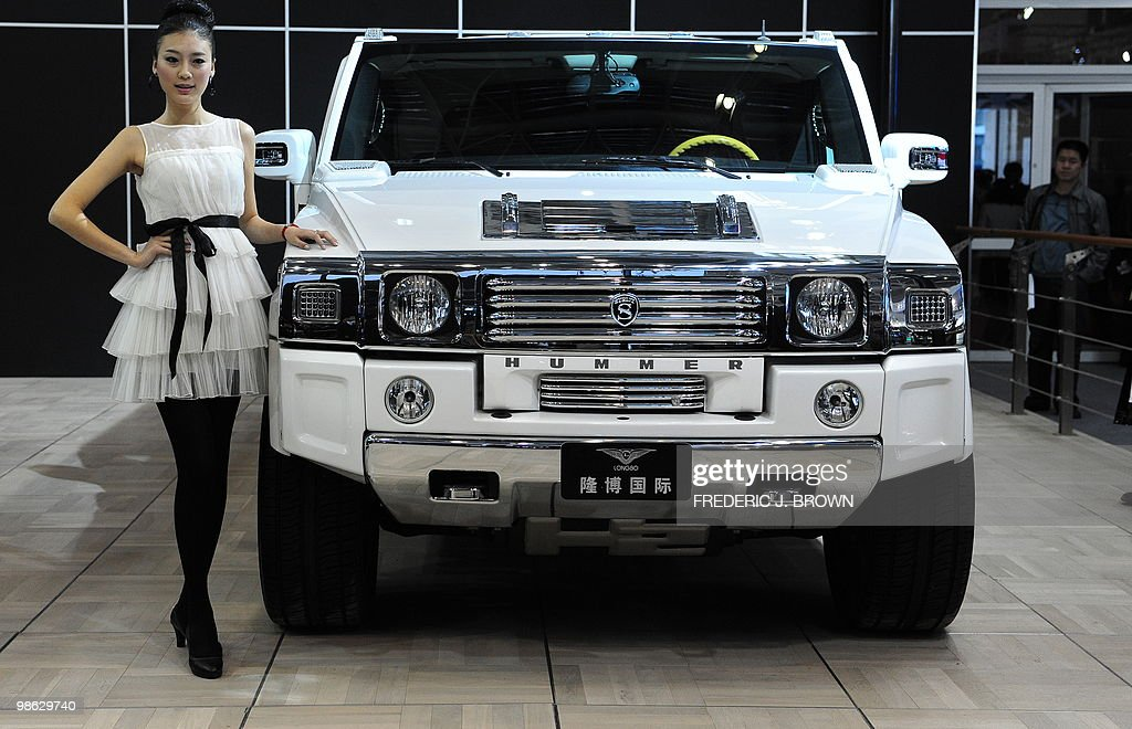 A model poses besides a Longbo customized Hummer H2-G during a media preview at the Beiijng Auto Show on April 23, 2010. Auto sales in booming China hit 13.64 million in 2009, overtaking the United States, as increasingly well-off Chinese consumers continued to snap up cars, helped by government incentives such as lower taxes. AFP PHOTO/Frederic J. BROWN