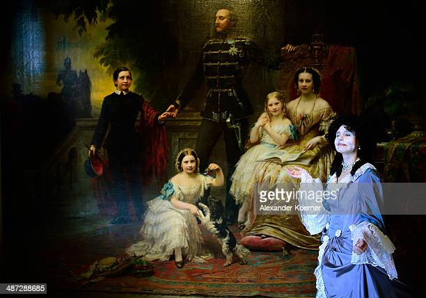 A model poses for photographers in front of a family painting of King George V and his family from 1851 during a preview of 'Der Weg zur Krone Das...