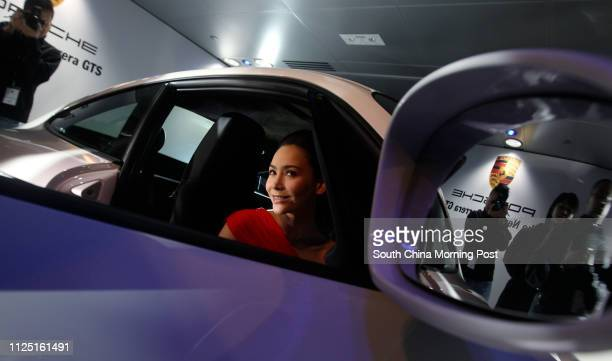 A model poses for picture with the new Porsche 911 Carrera GTS during the media preview at Porsche showroom Wan Chai 08MAR11