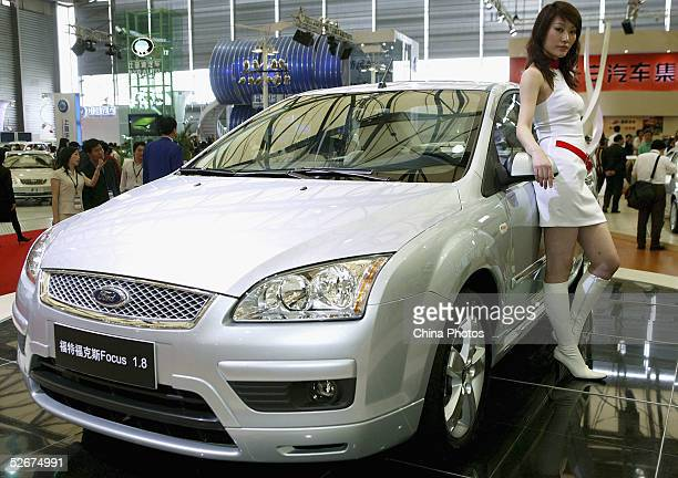 A model poses for pictures with a Ford Focus car at the Auto Shanghai 2005 Exhibition on April 21 2005 in Shanghai China Top world automakers will...