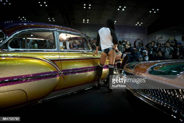 A model poses for the cameras next to the custom hot rod car is shown during the 26th Annual Yokohama Hot Ror Custom SHow 2017 December 3 2017 in...