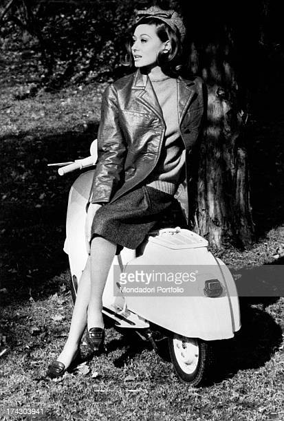 A model poses for the fashion photo shoot for the fashion magazine Confidenze resting on a white Vespa Special classic mid '60s wearing an aerpel...
