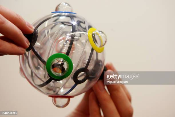 A model poses for the media with a Rubik's 360 a game cube featuring six balls trapped within three transparent plastic spheres during the 60th...