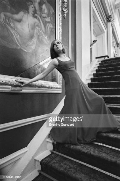 Model poses in a crepe evening dress in the crush bar of the Royal Opera House in London, UK, 21st November 1966. Behind her is a painting of 'Hera,...