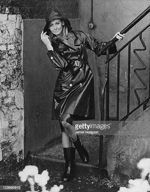 A model poses in a dark hooded raincoat and boots circa 1965