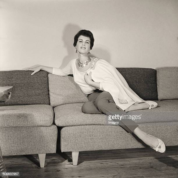 Model poses in a pantsuit by W.F. Adlmueller in the living room of Barbara Pflaum. 1957. Photograph by Barbara Pflaum . .