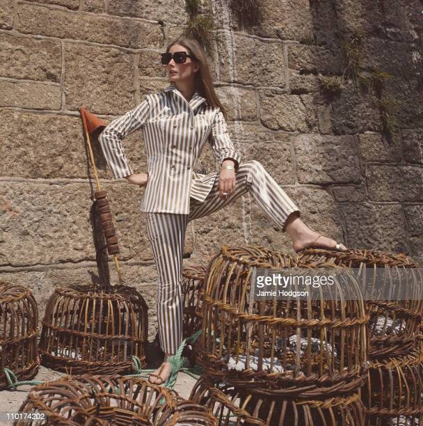 A model poses in a striped trouser suit circa 1965