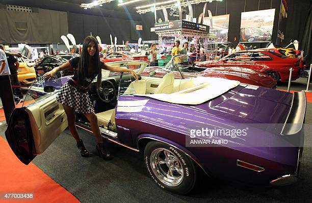 A model poses in front of a Dodge Challenger car displayed during the Lebanon Motorsport and Tuning Show on June 13 2015 in Jounieh north of Beirut...