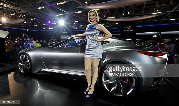A model poses in front of Hyundai's Venace sedan at the 12th Auto Expo opened for general public in Greater Noida on the outskirts of New Delhi on...