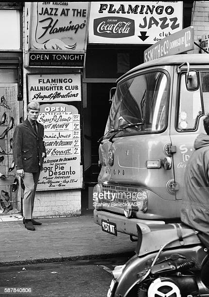 A model poses in the street outside the Flamingo club in Soho wearing Cecil Gee clothes for 'Mods Monthly' magazine London circa 1965