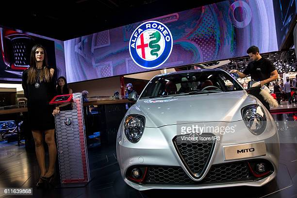 A model poses next the new Alfa Romeo MiTo during the press preview of the Paris Motor Show at Paris Expo Porte de Versailles on September 30 2016 in...