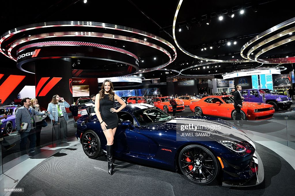 A model poses next to a 2016 Dodge Fiber ACE during the press preview of the 2016 North American International Auto Show in Detroit, Michigan, on January 11, 2016.