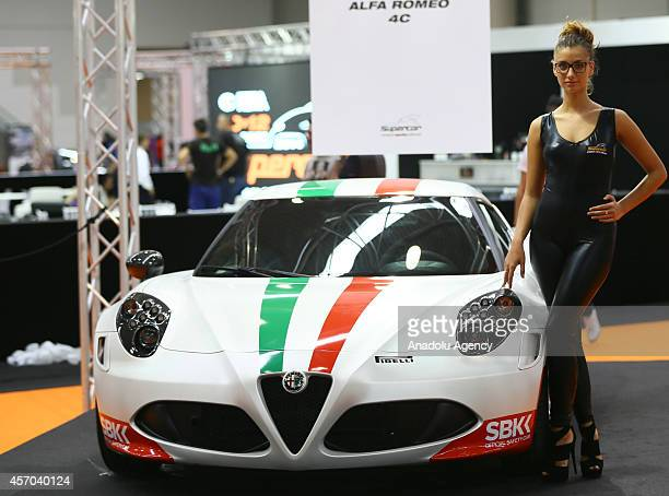 A model poses next to a Alfa Romeo 4C presented during the Supercar Roma Auto Show in Rome capital city of Italy on October 10 2014
