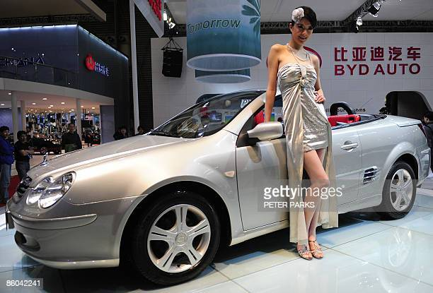 Model poses next to a car by Chinese automaker BYD at Auto Shanghai 2009, China's largest auto show on April 20, 2009. Carmakers from around the...