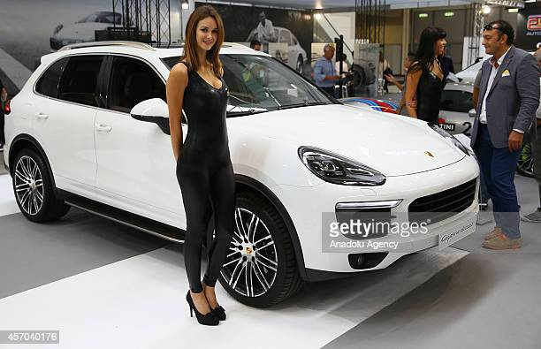 A model poses next to a Porche Cayenne Diesel presented during the Supercar Roma Auto Show in Rome capital city of Italy on October 10 2014