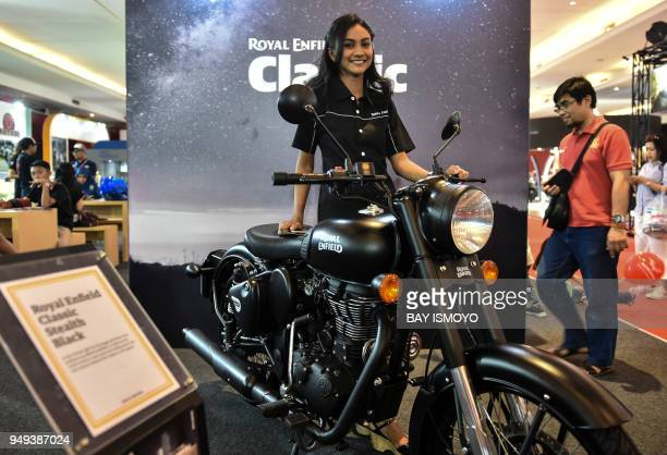 A model poses next to a Royal Enfield motorcycle during the 2018 Indonesia International Motor Show in Jakarta on April 21 2018