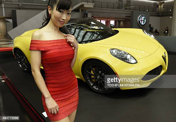 A model poses next to an Alfa Romeo 4C Spider at the Tokyo Motor Show in Tokyo on October 29 2015 The biennial motor show's 44th edition which runs...