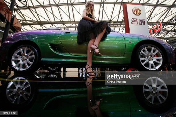 Model poses next to an MG sports car during the Auto Shanghai 2007 event on April 20, 2007 in Shanghai, China. More than 1,300 car makers and car...