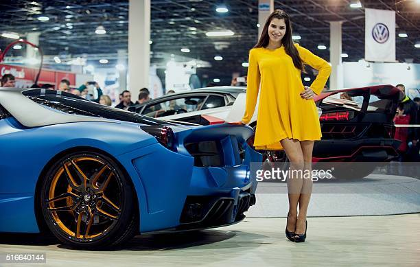 A model poses next to cars exhibited during a threeday auto motor and tuning show at the Hungexpo Budapest Fair Center in Budapest on March 18 2016 /...