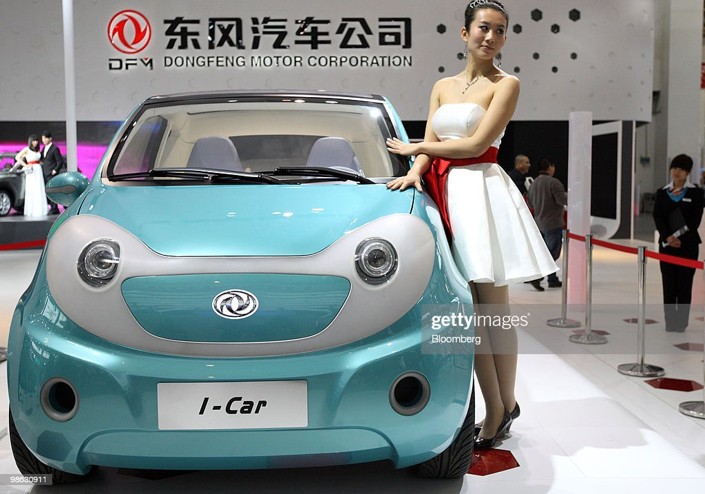 A model poses next to Dongfeng Motor Group Co.'s I-Car concept vehicle, displayed at the Beijing Auto Show in Beijing, China, on Friday, April 23, 2010. The show will be held through April 27. Photographer: Tomohiro Ohsumi/Bloomberg via Getty Images