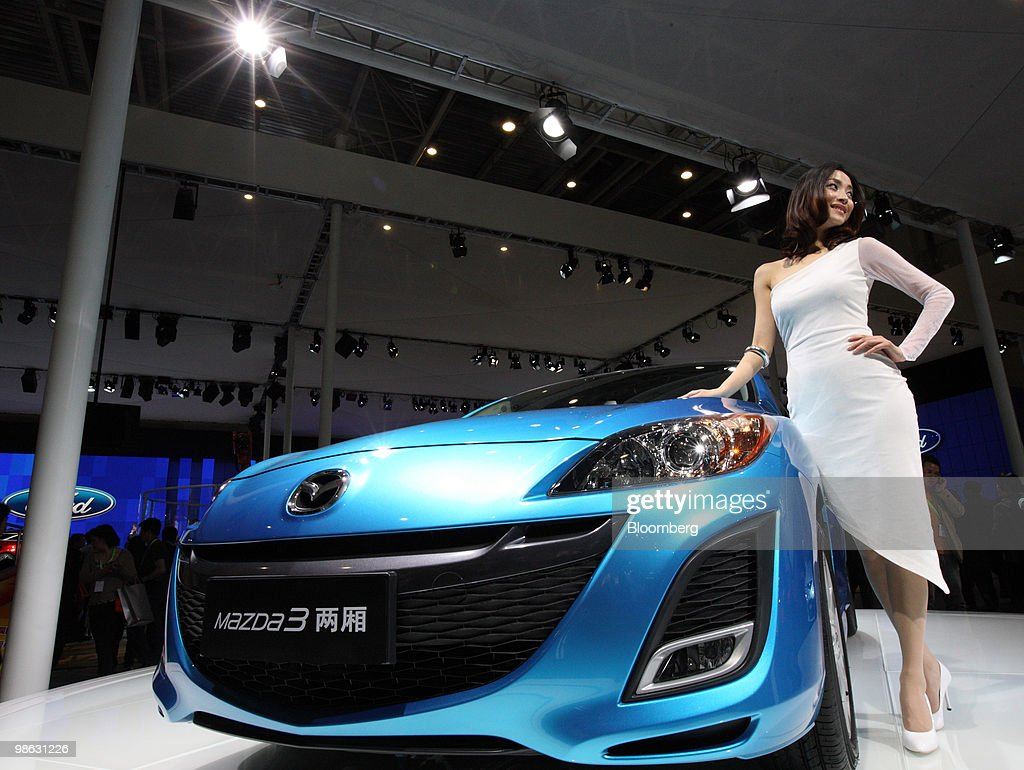 A model poses next to Mazda Motor Corp.'s Mazda 3, displayed at the Beijing Auto Show in Beijing, China, on Friday, April 23, 2010. The show will be held through April 27. Photographer: Tomohiro Ohsumi/Bloomberg via Getty Images