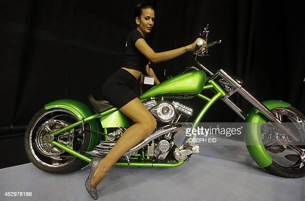A model poses on a chopper motorcycle during the Lebanon Motorsport and Tuning Show 2014 in Jounieh north of Beirut on July 31 2014 The show...