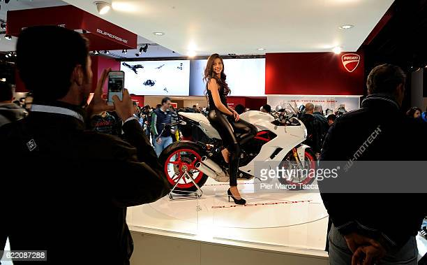 A model poses on the new supersport Ducati motorcycle during the EICMA 2016 74th International Motorcycle Exhibition on November 9 2016 in Milan...