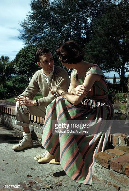 Model poses wearing a 1940's striped summer dress while talking to a man.