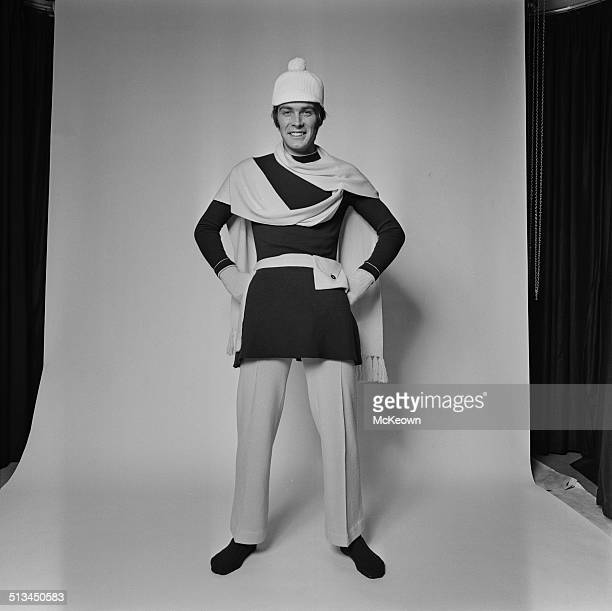 A model poses wearing a long sweater knitted trousers scarf and bobble hat 14th October 1969